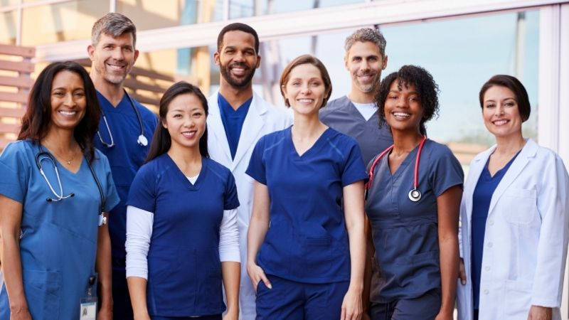 Group of multicultural diverse travel nurses happy and smiling in scrubs.