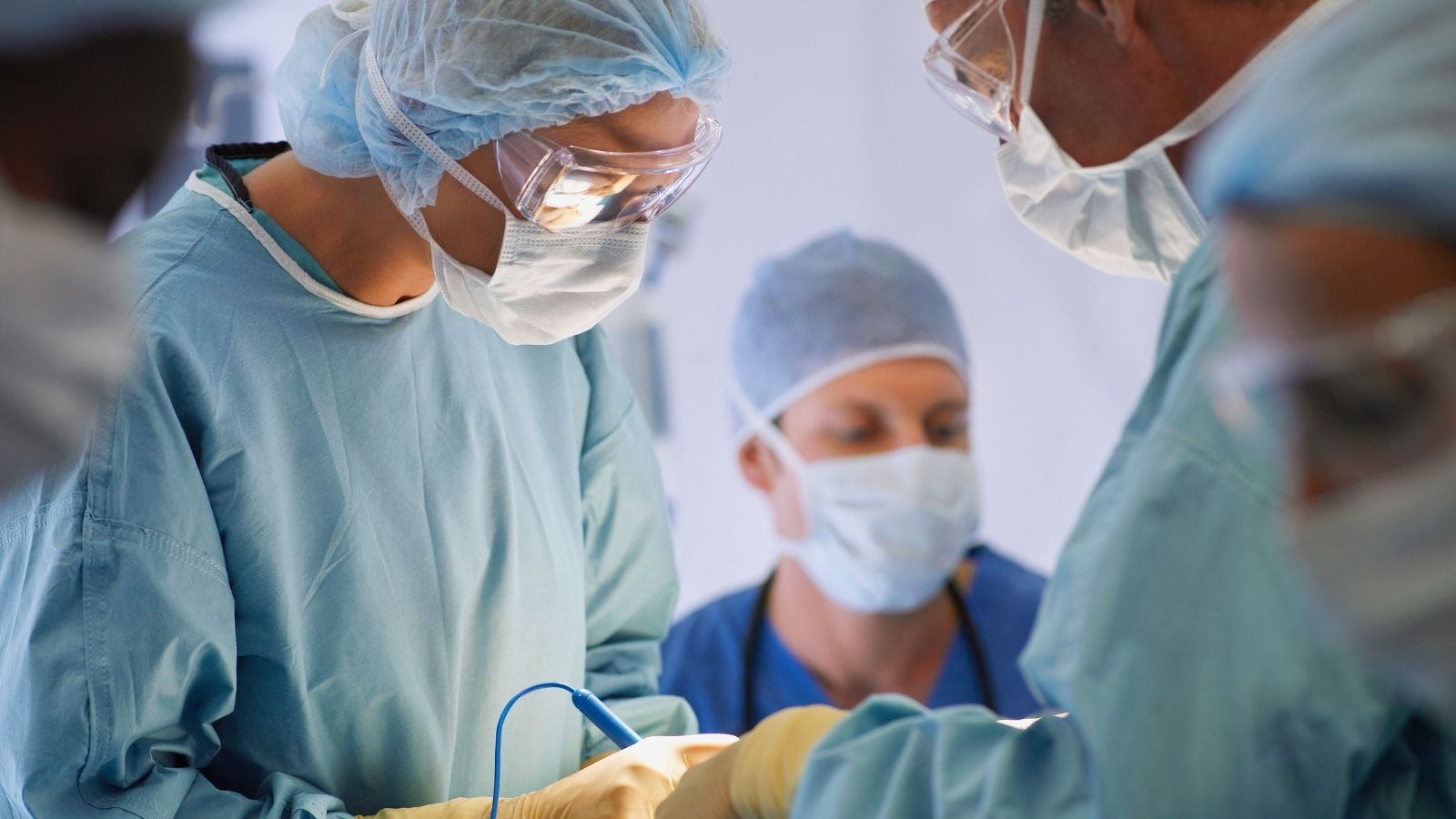 Travel allied health helping with a surgery operation while wearing scrubs.
