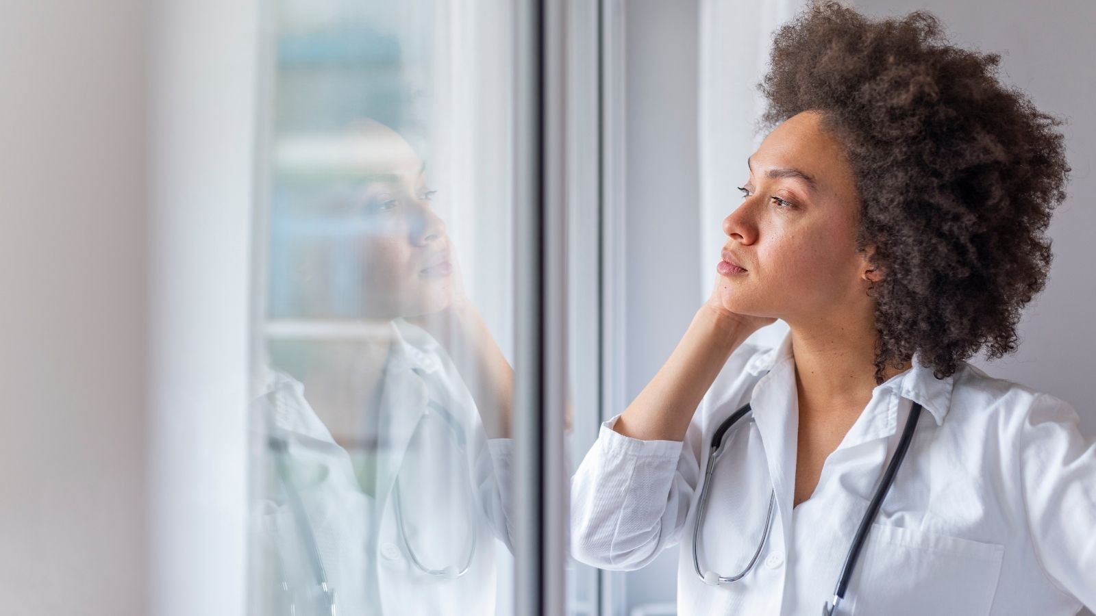 Sad female nurse in uniform staring out the window thinking.