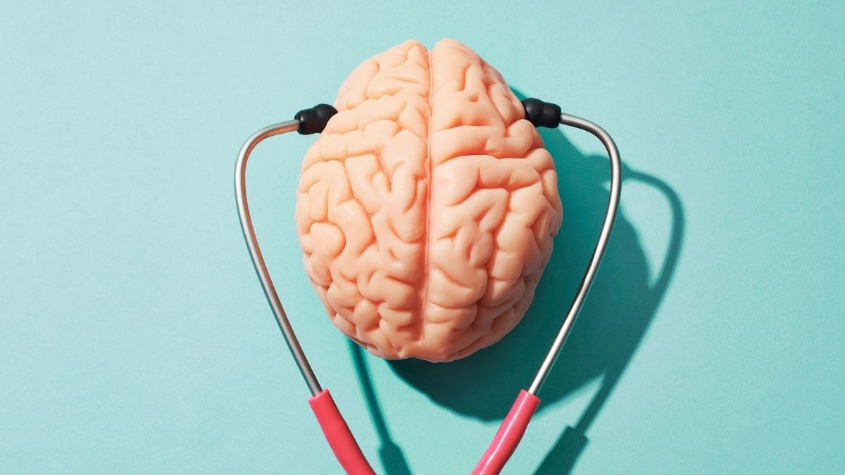 Pink rubber brain on a turquoise background with a stethoscope.