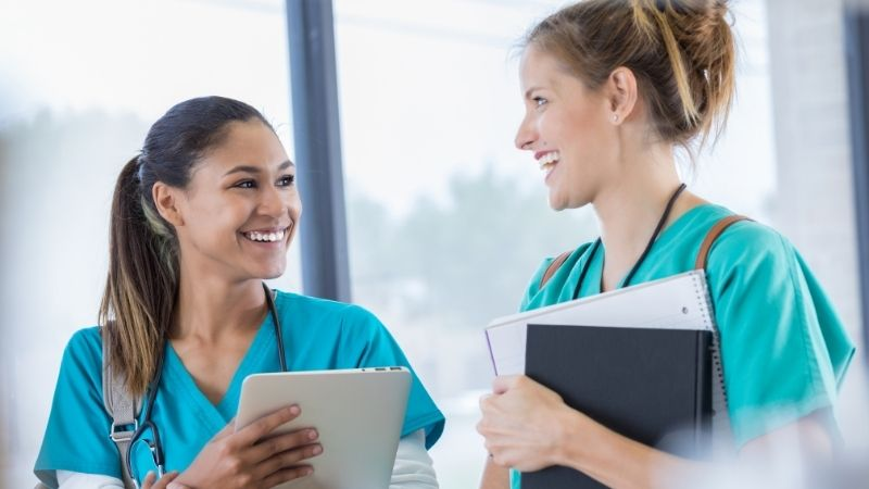 Friends travel nursing in pairs working together and smiling at each other.