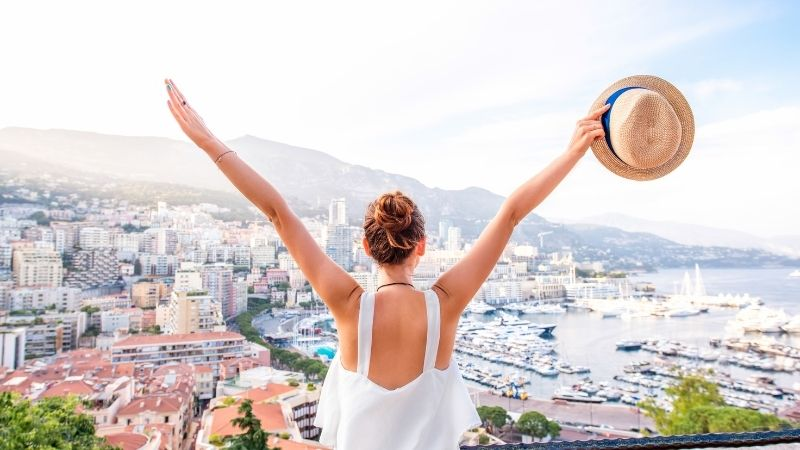 Woman happy with arms up facing a top destination skyline with mountains.