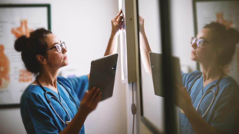 Female nurse with glasses examining x-rays on a light box.