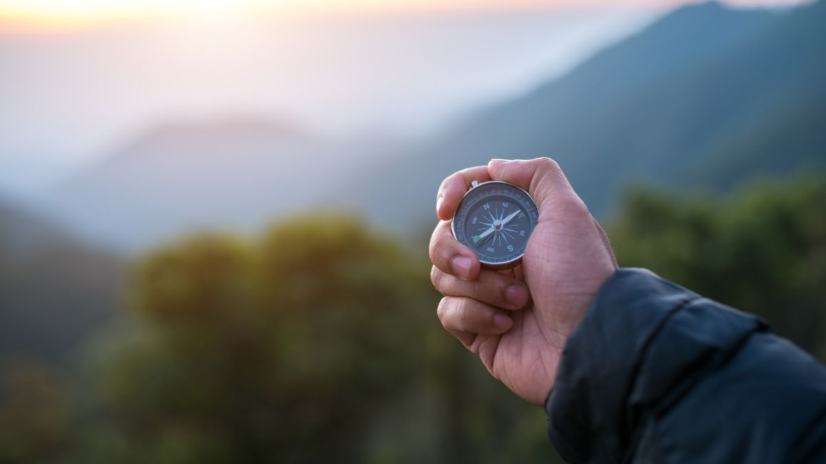 Traveler holding compass in hand on a hike in nature.