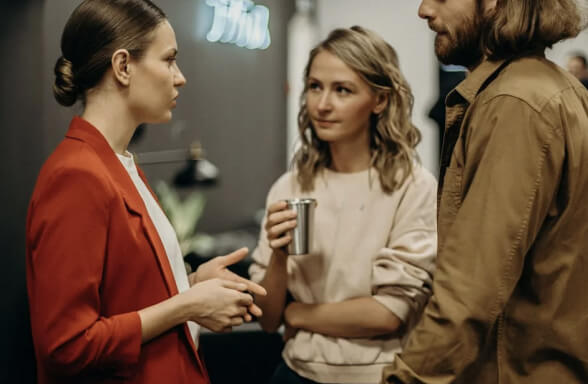 image of two females and one male chatting in the office