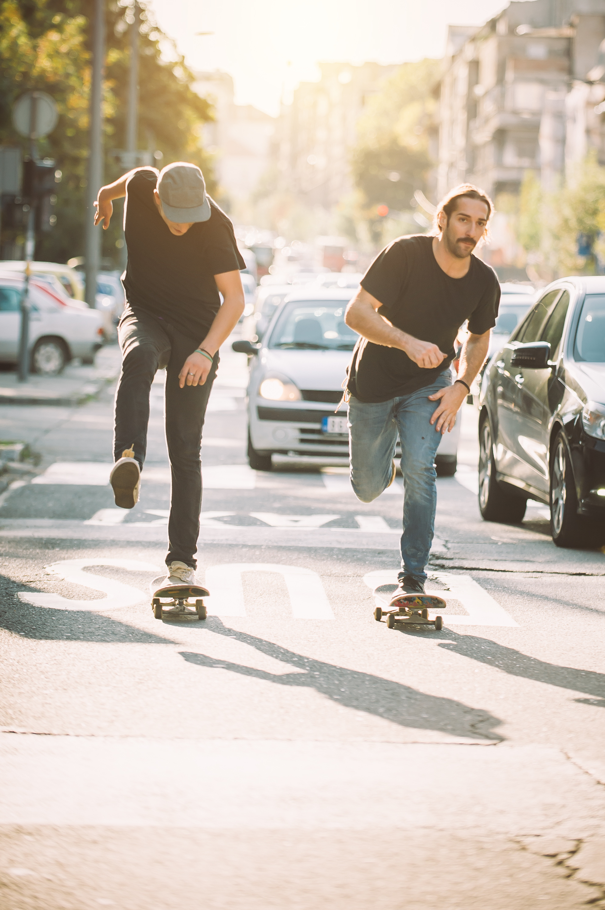image of two males both riding skateboards in the bus/taxi lane through traffic