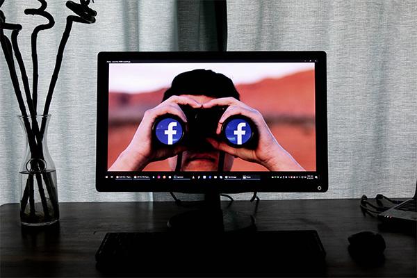 man looking through facebook binoculars