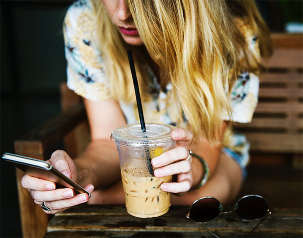 woman texting holding coffee