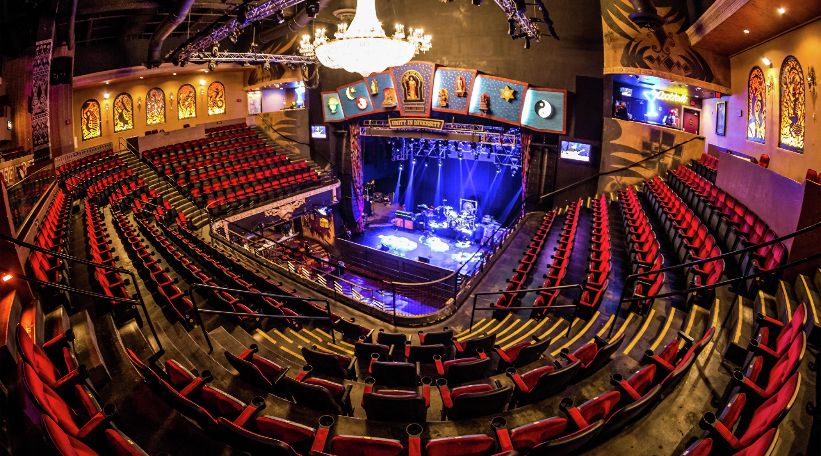 image of what House of Blues looks like. Big theater with red seats and a stage in the center.