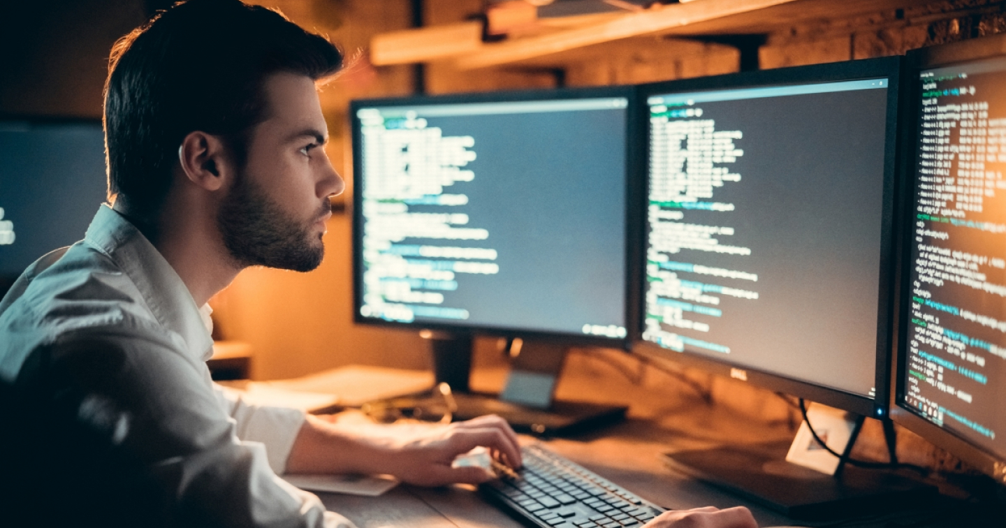 Man sitting in front of three monitors with code.