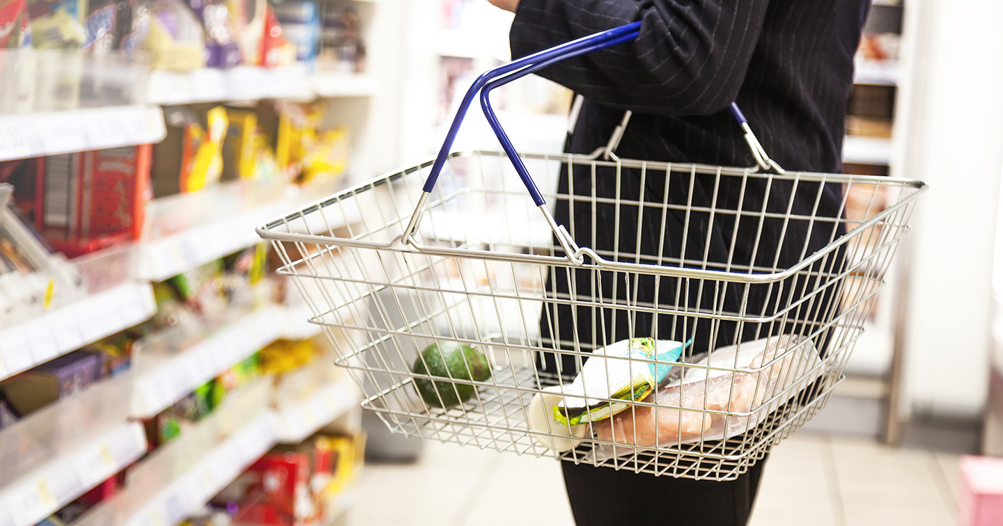 Person shopping holding a grocery basket