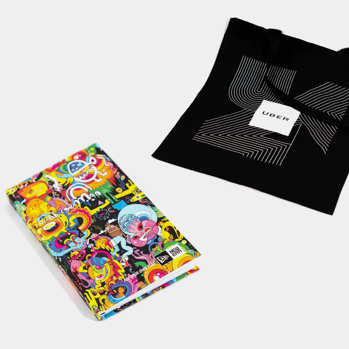 Background image of silk screen printed Uber tote bag and new era colourful printed notebook