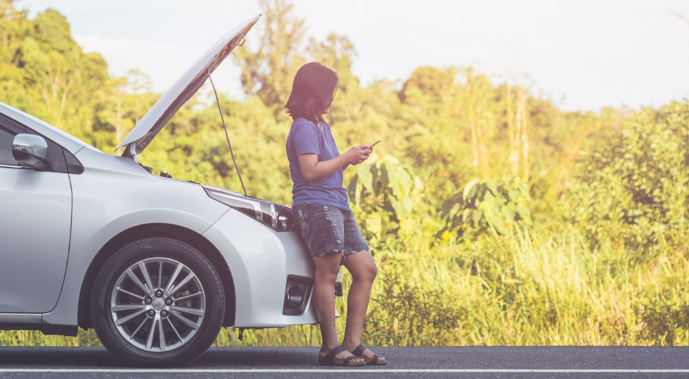 Woman standing at car on phone