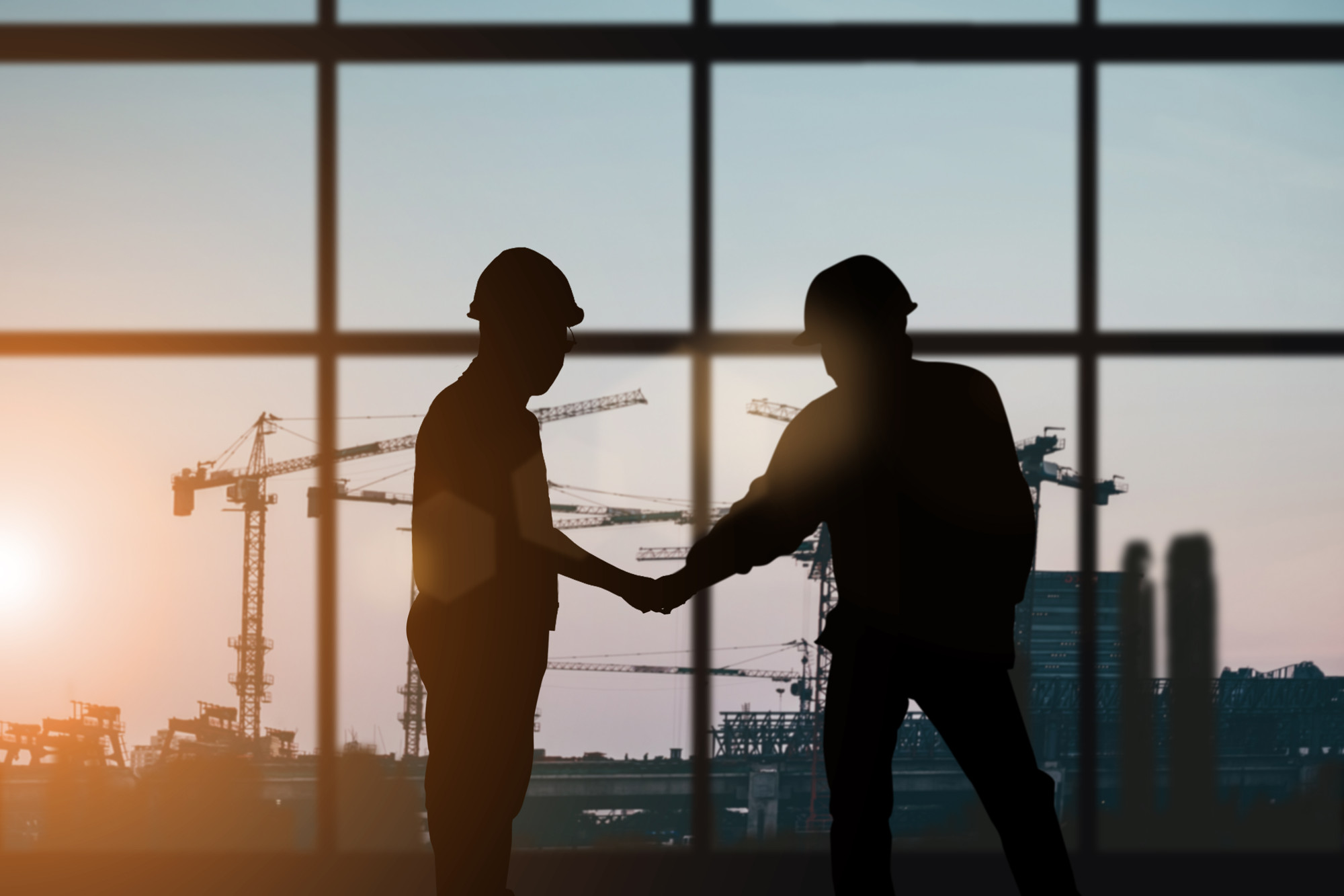 two men on construction site shaking hands in agreement