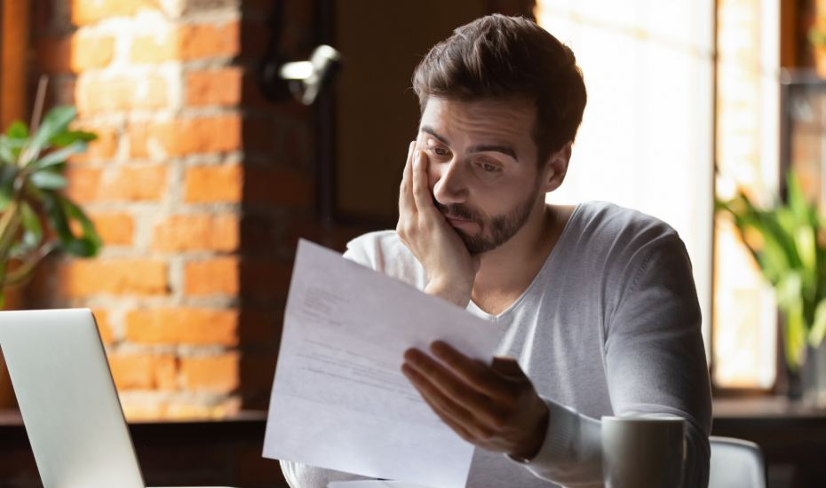 a man looking frustrated whilst reading a business letter in a cafe