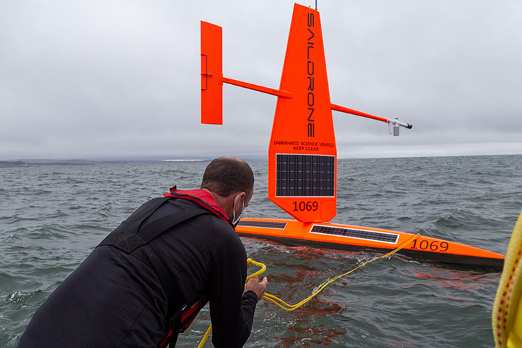 Saildrone employee wearing face mask deploys vehicle in Pacific Ocean