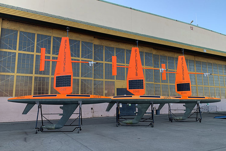 Three Saildrone uncrewed surface vehicles sitting on cradles in Alameda, CA