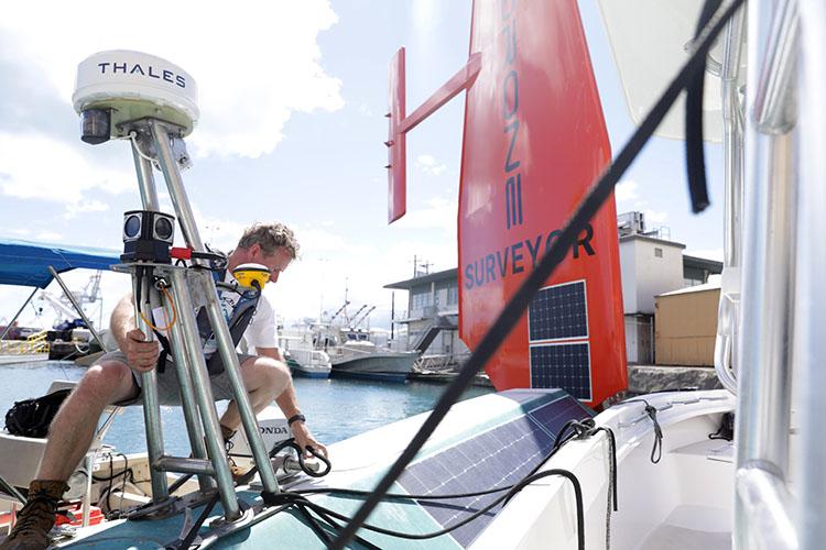 Saildrone founder & CEO Richard Jenkins on the hull of the Saildrone Surveyor