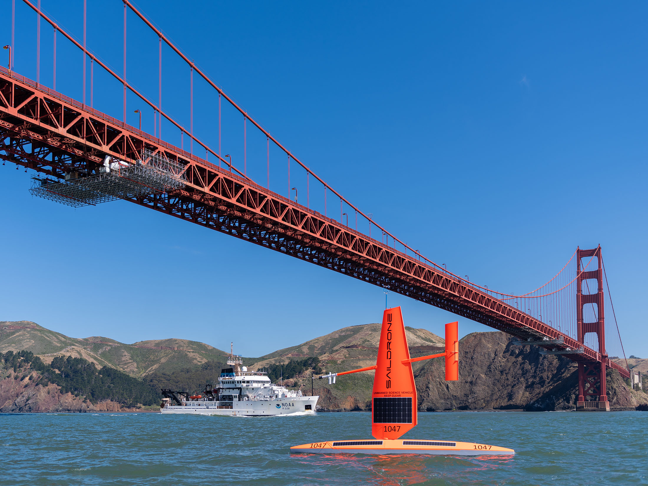 Saildrone USV and NOAA research vessel Reuben Lasker under Golden Gate Bridge