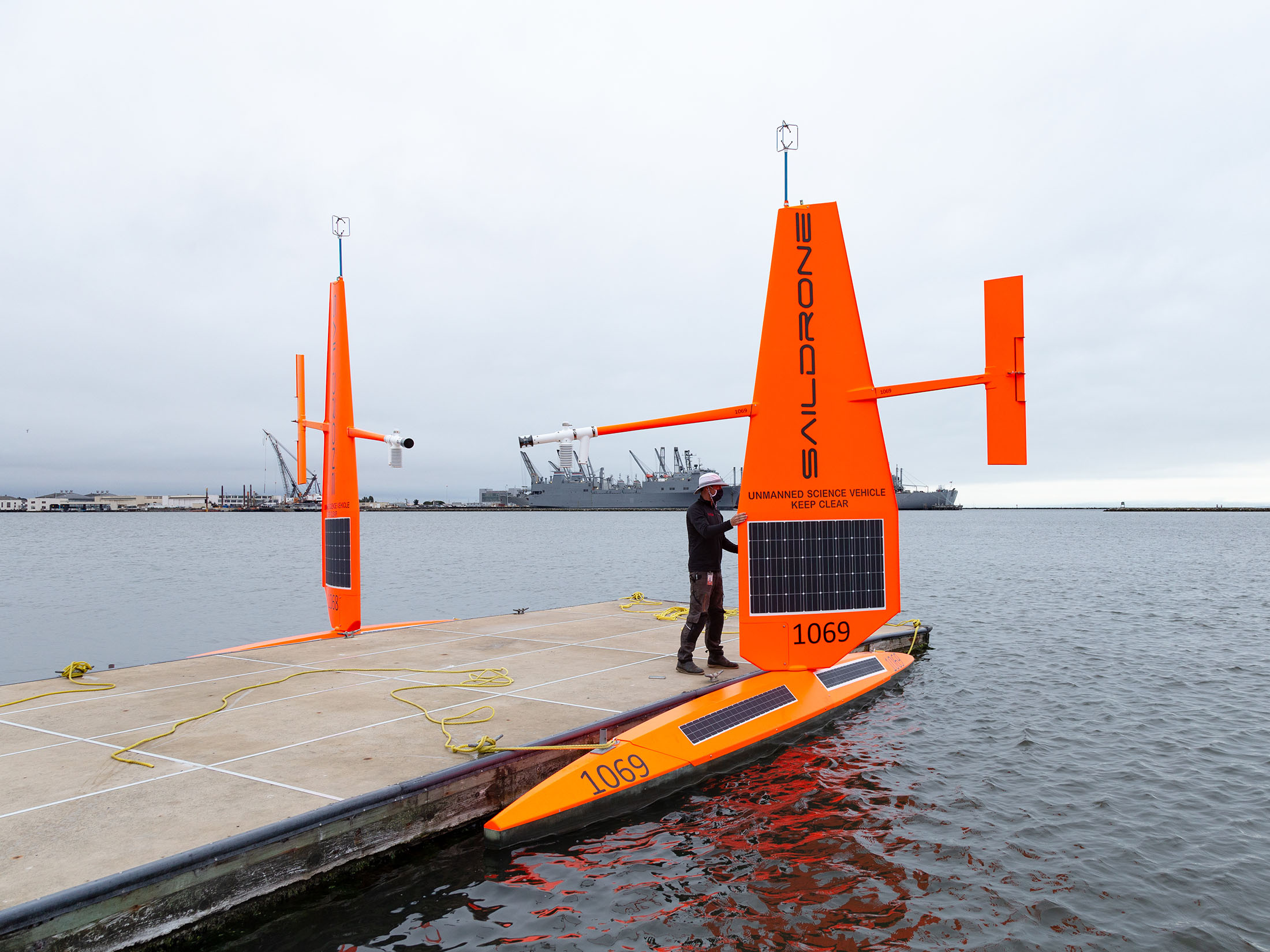 Saildrone at dock with worker wearing mask for COVID-19
