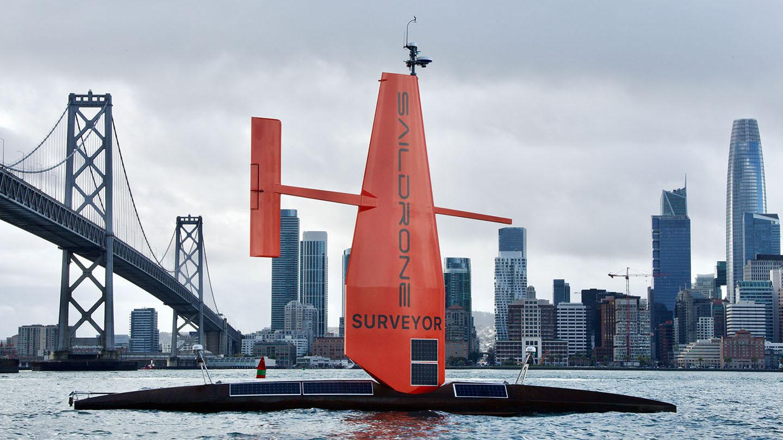 Saildrone Surveyor sailing in front of the Bay Bridge and San Francisco skyline.