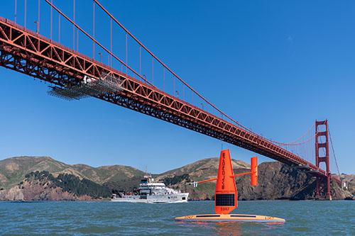 Saildrone USV and NOAA research vessel Reuben Lasker under Golden Gate Bridge