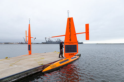 A Saildrone employee wearing a mask for COVID-19 inspects a USV at the dock in Alameda before deploying it to the Arctic.