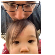 Father kissing his daughter's head as they take a close up selfie