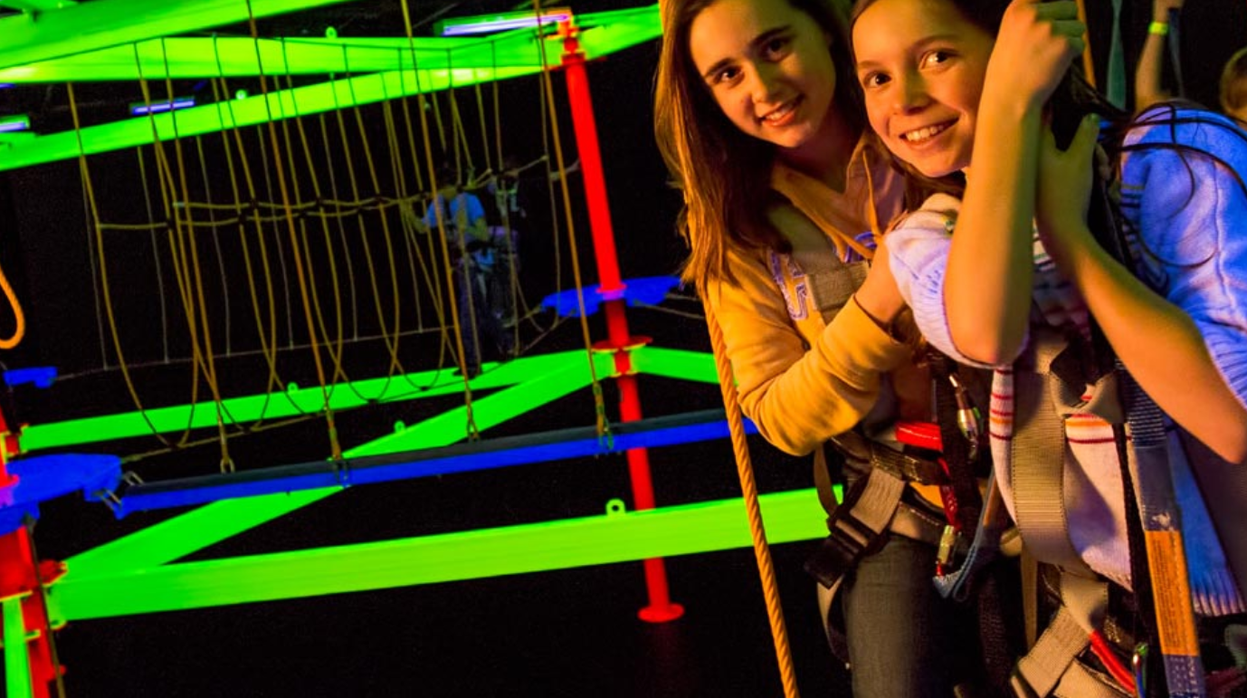 two young adult on glow in dark ropes course