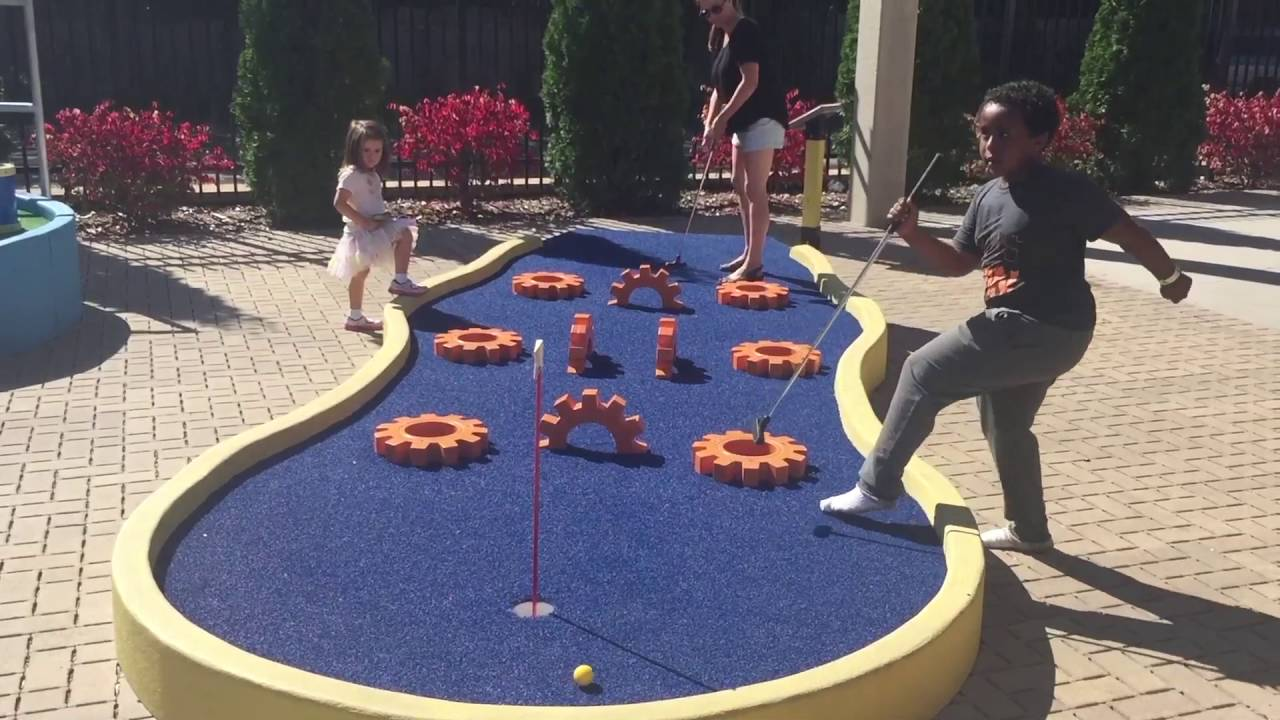 happy family playing mini golf
