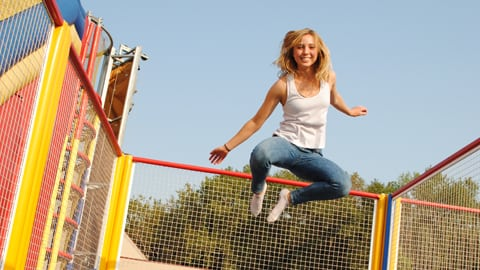 happy woman jumping on trampoline