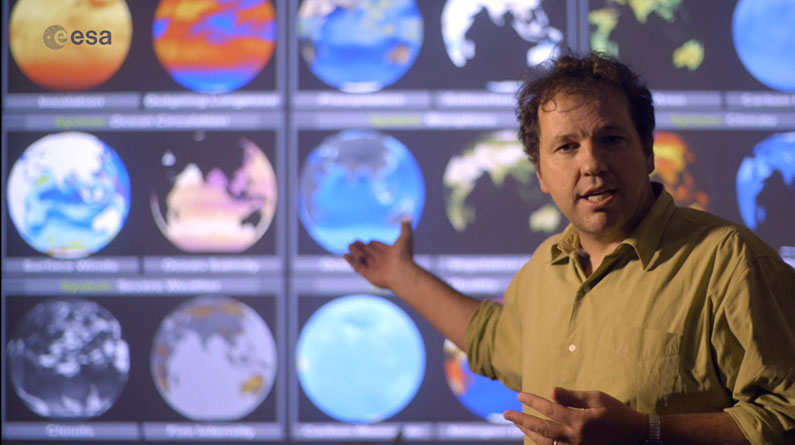 Photo of Professor Martin Wooster standing in front of a screen showing various images of Earth