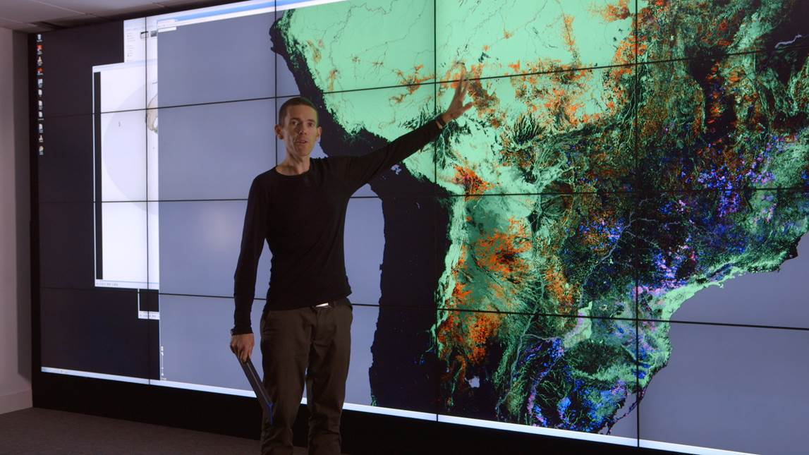 A photo of Dr Mathius Disney pointing at a large screen behind him, with a map of South America on it.