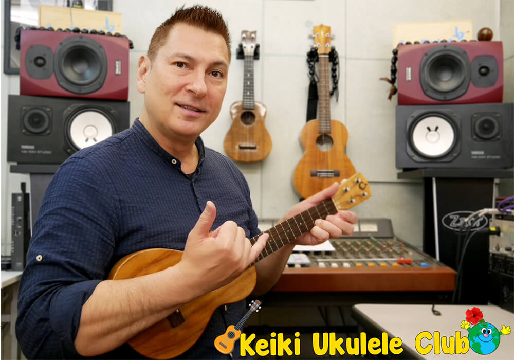 Joy to the World owner, Jerry, posing with his ukulele, giving a shaka sign with his hand.