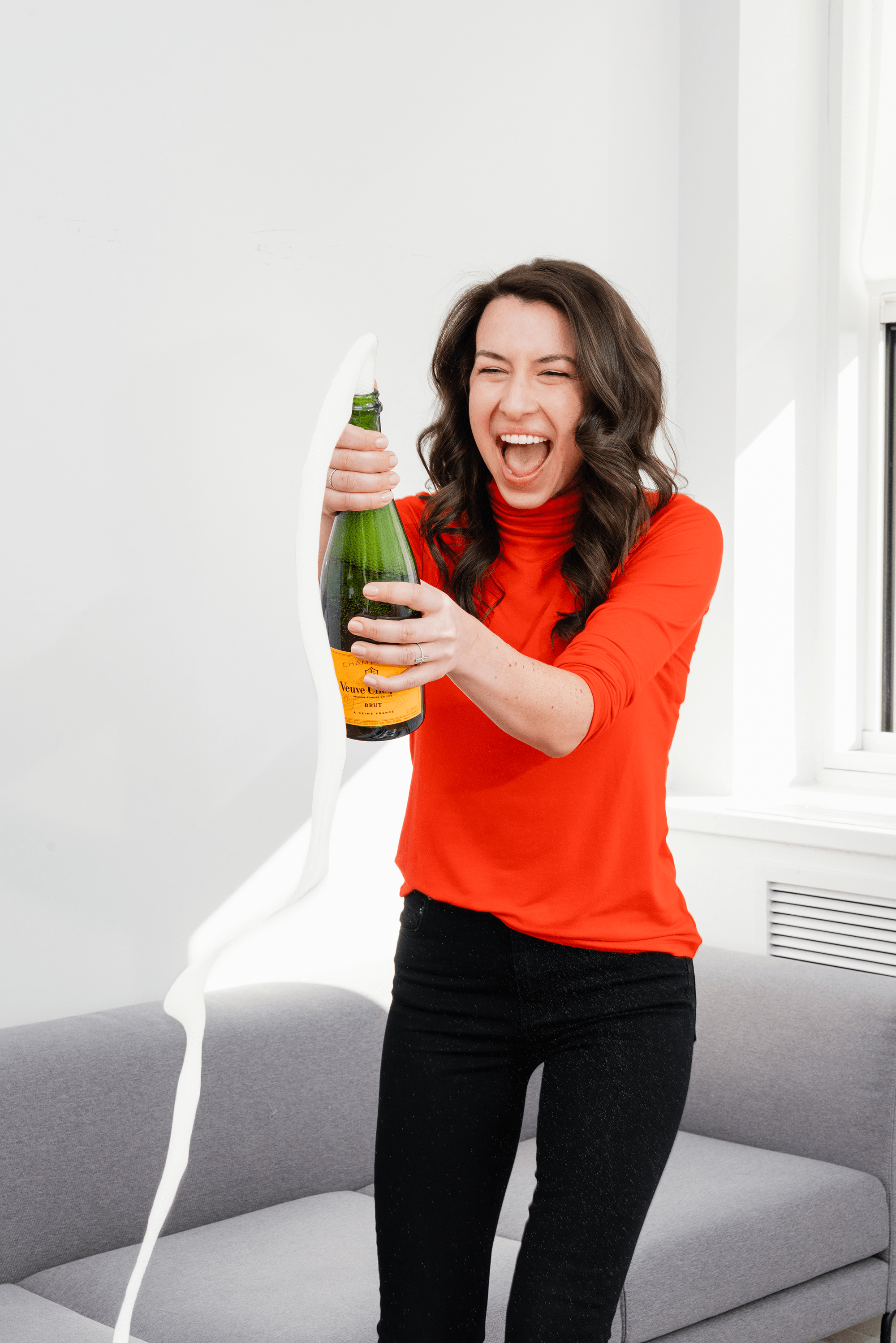 Woman opening a bottle of champagne