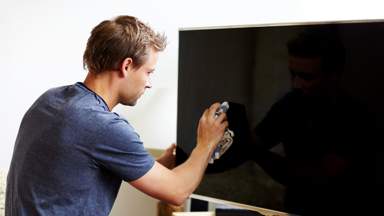 Man using a cloth to wipe down a flat screen TV