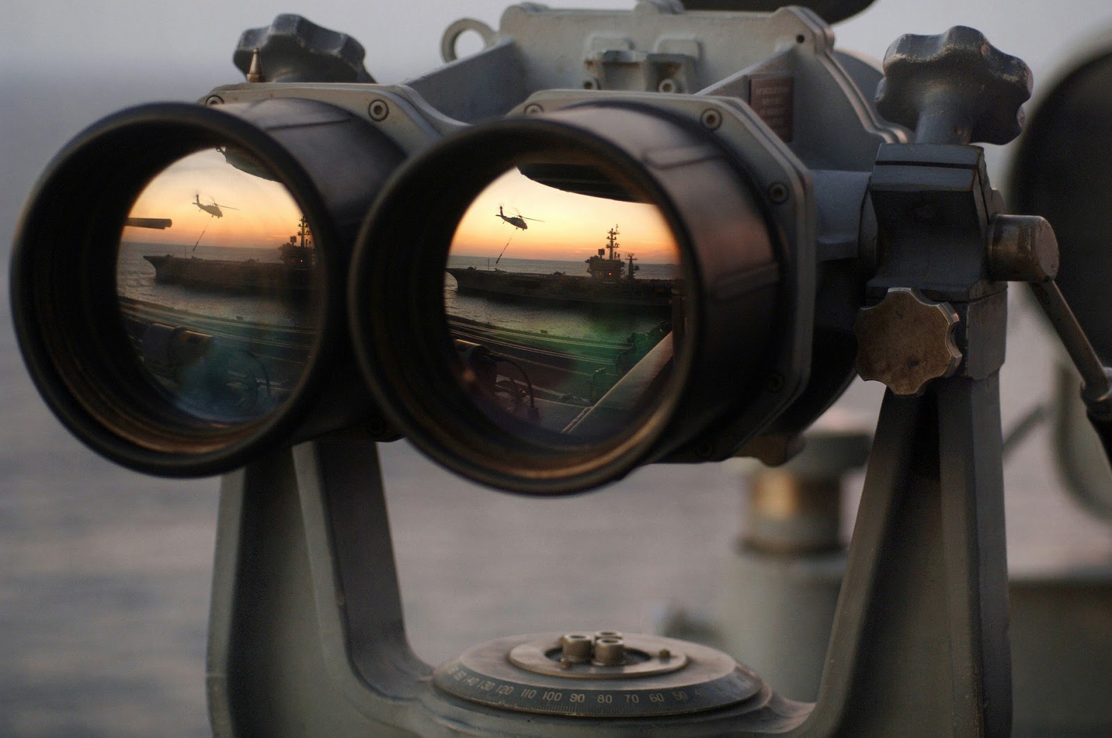 Binoculars spying on a military ship and helicopter