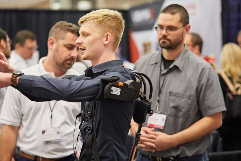 Attendee tries on an exoskeleton on the exhibition floor of the Enterprise Wearable Technology Summit
