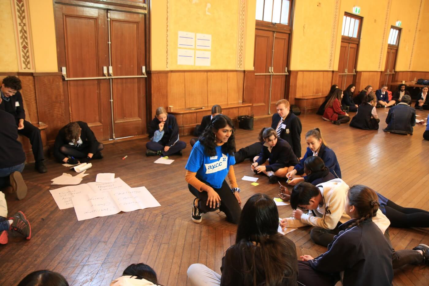 Grace facilitates a workshop with school children in a school hall.