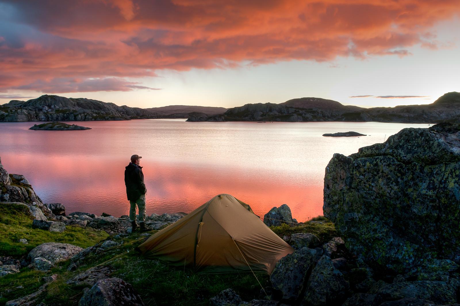 Mann og telt i solnedgang