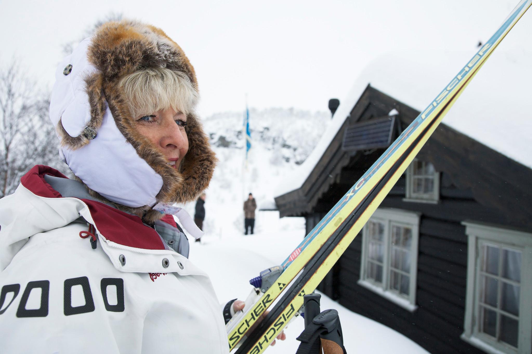Dame med ski utanføre hytte