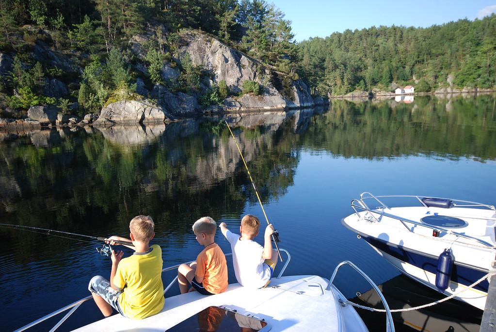 Gutar som fisker ved båtane
