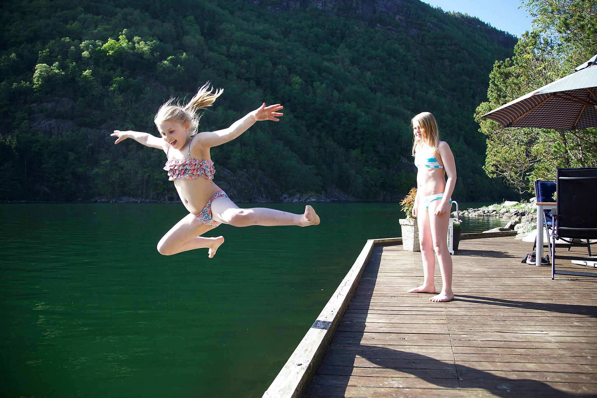 Jenter som hopper i vatnet frå ei brygge