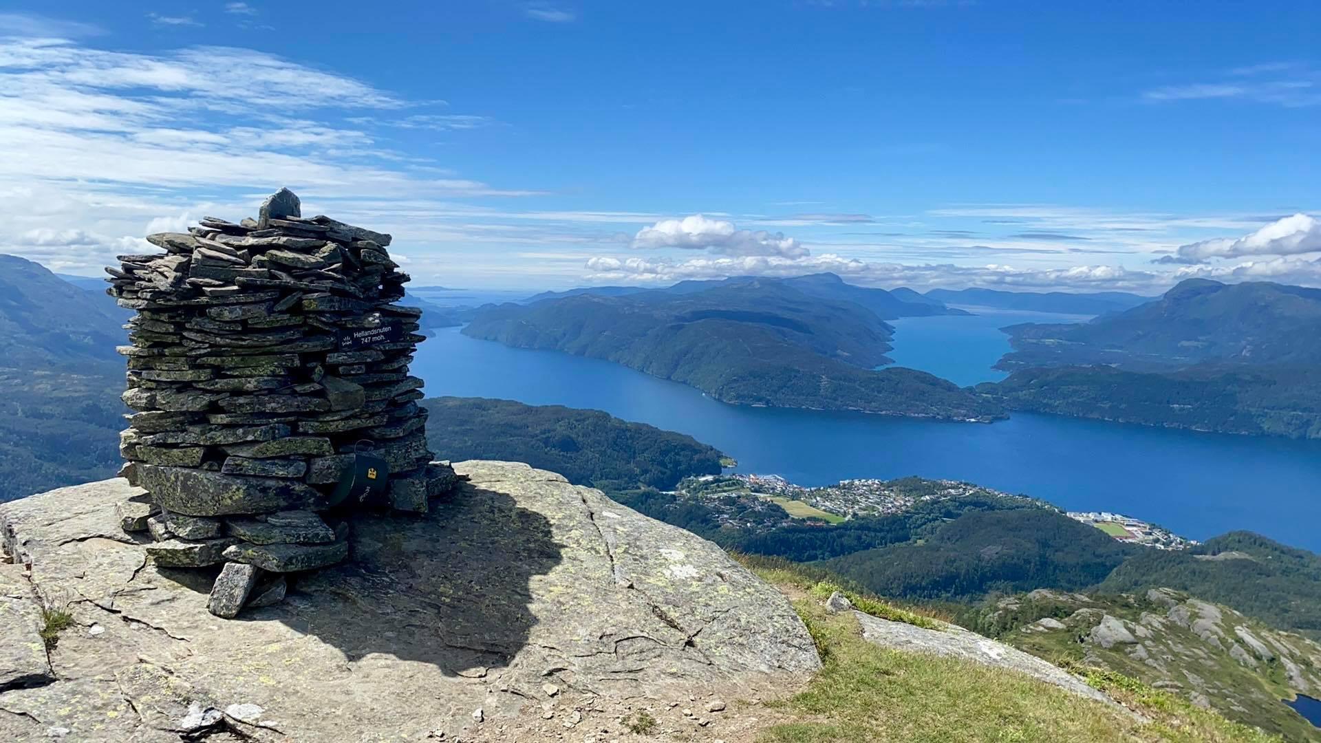Varde på toppen av fjelltopp med utsikt over fjordlandskap