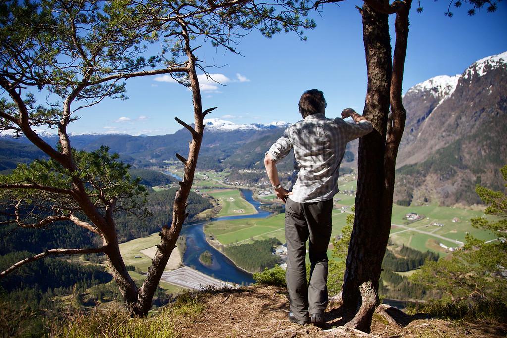 Mann på fjelltopp som ser utover grend