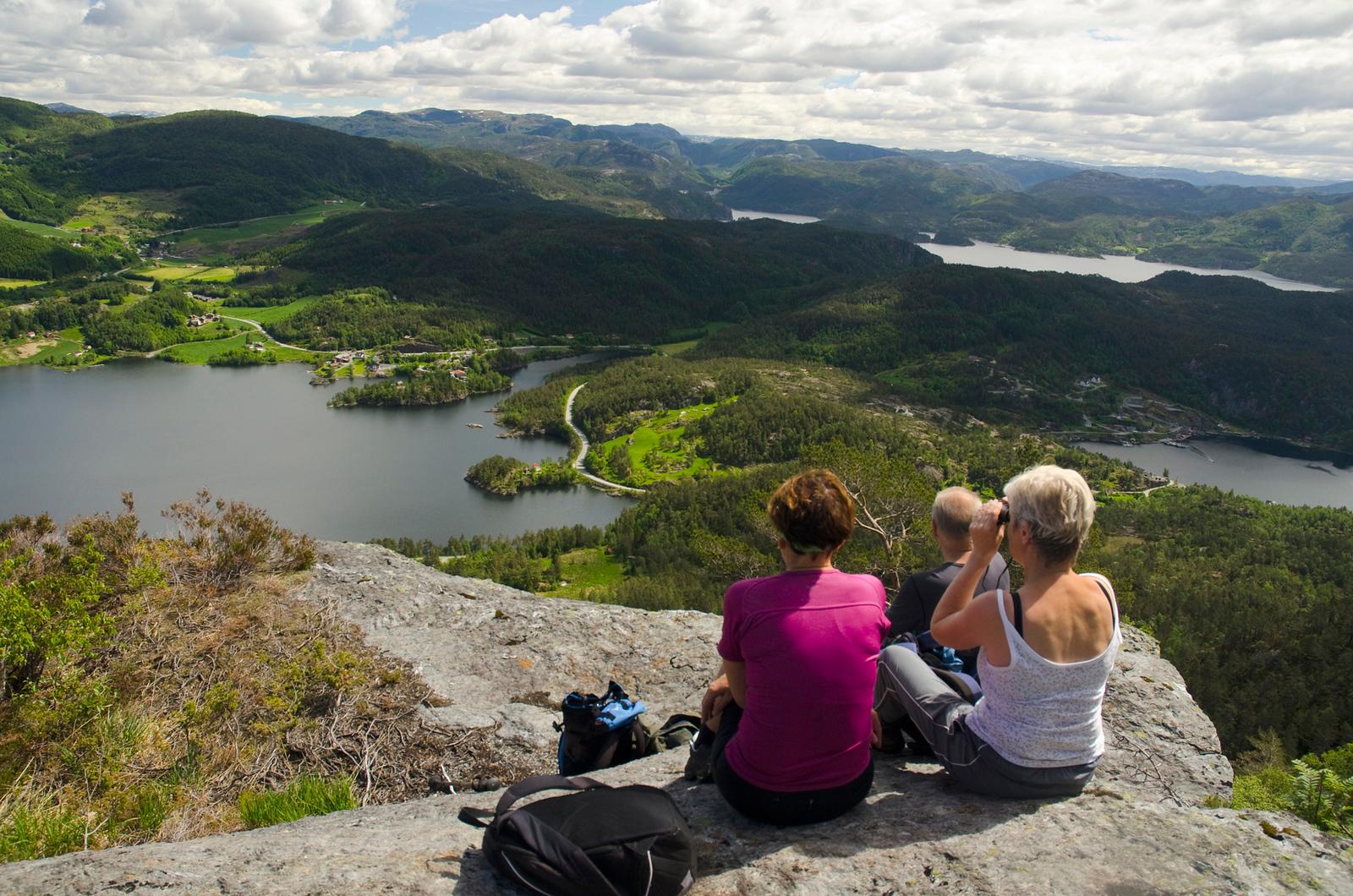 Menneske på fjelltopp som ser utover naturlandskap
