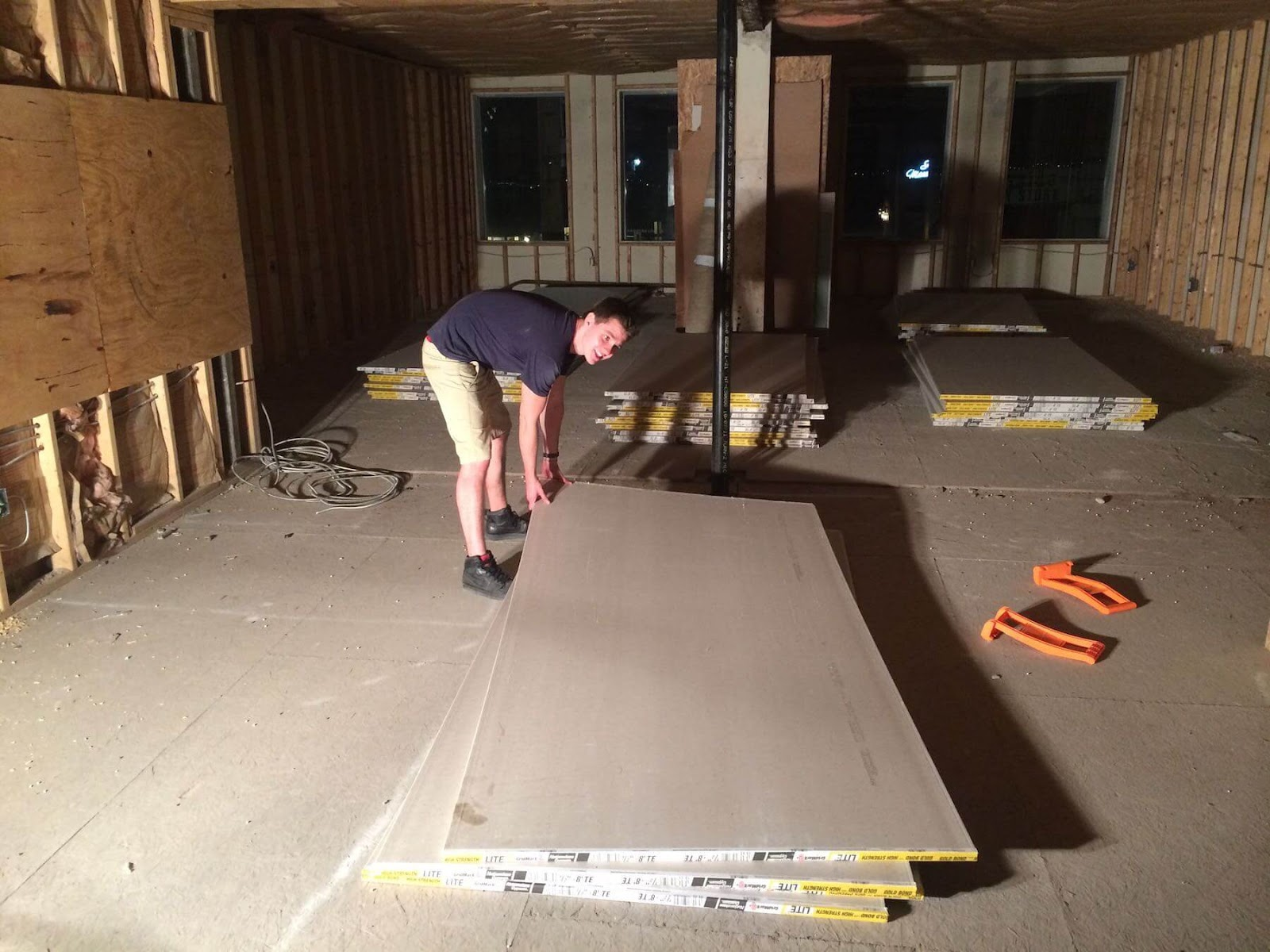 young man picking up drywall