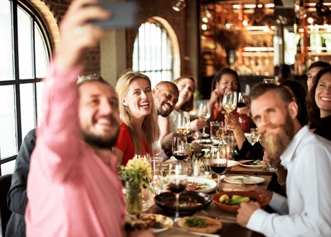 people at a restaurant taking a selfie