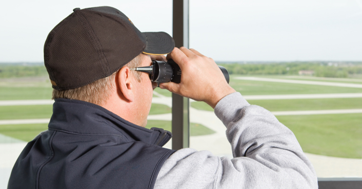 Man looking out over airport runways with binoculars