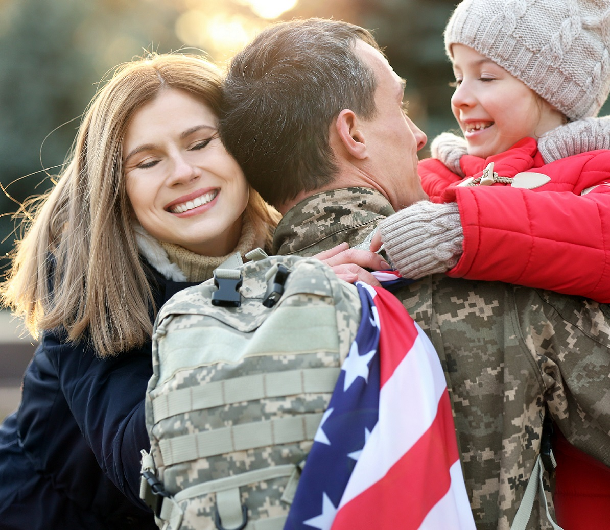 soldier hugging family in military uniform and flag draped over shoulder